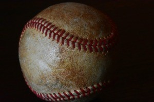 An old baseball on a black background.