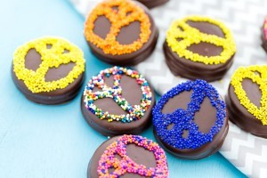 Chocolate coated sandwich cookies with sprinkles in the shape of a peace sign.