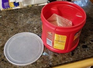 A recycled coffee container with a plastic lid next to it.