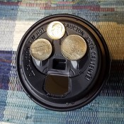 Coins on top of a paper cup with a plastic lid.