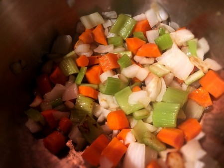 A mix of vegetables being sauteed as a soup base.
