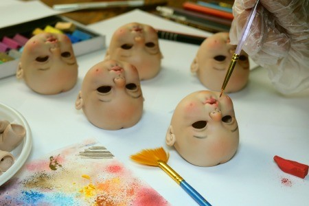 A collection of porcelain doll heads being painted.