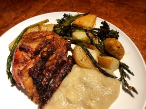 A plate of crispy pork roast with apple onion gravy & veggies.