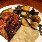 A plate of crispy pork roast with apple onion gravy & veggies.