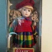 Value of a Classic Treasures Porcelain Doll - blond haired doll wearing a red beret, red sweater vest over a long sleeve plaid dress