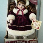 Value of a Collector's Choice Musical Porcelain Doll - doll wearing a white faux fur trimmed coat and hat