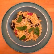 A dish of orzo tossed with sun-dried tomatoes, salami and parmesan.