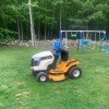 Battery Hooked Up Wrong on Cub Cadet - riding mower in large yard with swing set in background