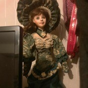 Identifying a Porcelain Musical Doll - doll with dark green and tan Victorian style dress and matching large hat, standing next to a computer monitor