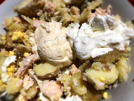 Mixing the chicken potato & egg with mayo & sour cream.