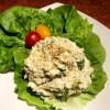 A serving of chicken potato egg salad on a lettuce leaf.