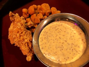 Spicy mustard dipping sauce next to fried foods.