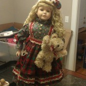 Value of a Collector's Choice Porcelain Doll? - doll wearing a print dress with a plaid apron and holding a teddy bear