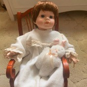 Identifying a Porcelain Doll? - doll in a rocking chair holding a stuffed bunny