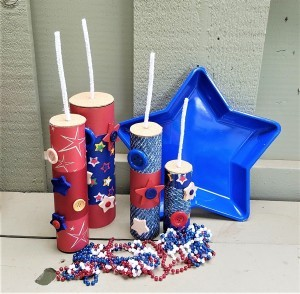 Faux Firecrackers - final display with plastic blue star bowl and red, white, and blue beads arrayed in front of the four firecrackers
