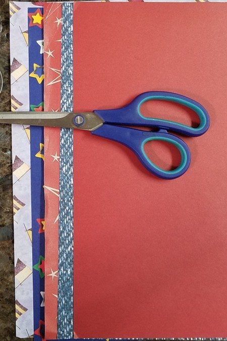 Faux Firecrackers - scissors laying on top of several pieces of scrapbook paper