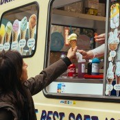 A woman receiving an ice cream cone from a truck.