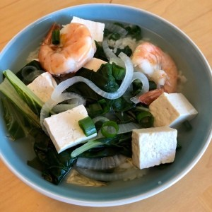 A bowl of bok choy tofu shrimp soup.
