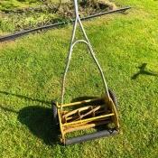 Value of Four Vintage Mowers - vintage yellow reel mower in yard