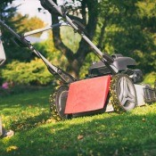 An older push mower being used on the lawn.