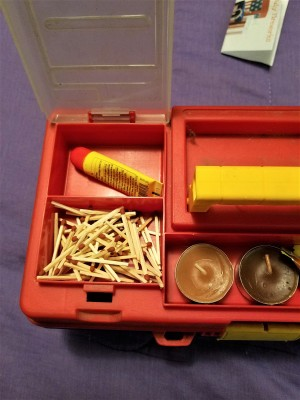 Supplies placed in the bottom of a tool box.