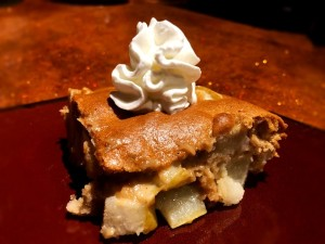 A piece of Juicy Pear Cake with whipped cream on top.