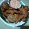 A plate of chicken and mojos with a dipping sauce.