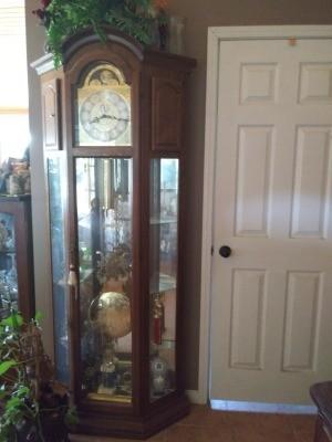 A beautiful grandfather clock next to a door.