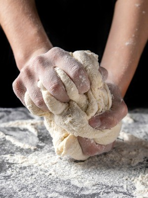 Bread dough being kneaded before baking.
