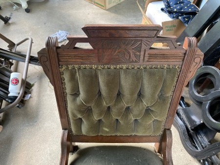 The carved top of an antique chair.