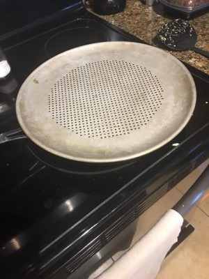 Makeshift Steamer - perforated pizza pan on top of skillet