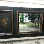A three part panel with mirror in center and fruit painted on the other two