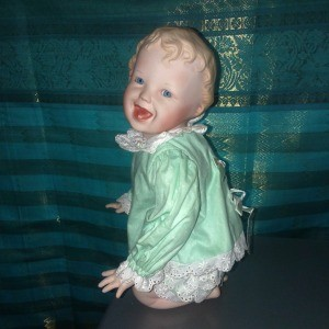 A kneeling porcelain doll in green.