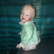 A kneeling porcelain doll in green.
