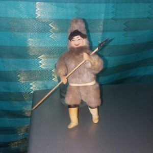 A doll standing holding a hunting spear