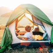 A small boy in a tent overlooking a valley.