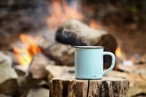 A coffee cup in front of a campfire.