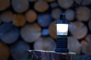 A lantern in front of a stack of wood.