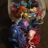 Several skeins of embroidery floss in a plastic container.