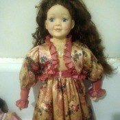 A doll with long dark brown hair wearing a light brown floral dress