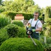 A man using a hedge trimmer.