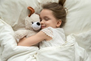 A little girl in bed with her stuffed animal.