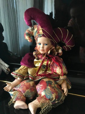 A porcelain doll in a colorful costume with a jester's hat.