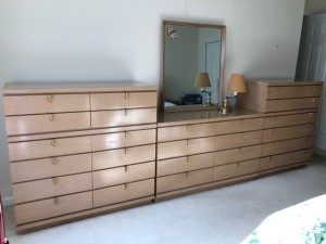 A long sectioned dresser with a mirror.