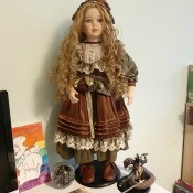 A blonde porcelain doll with old fashioned clothing.