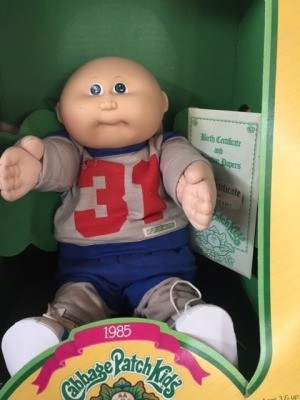 A Cabbage Patch doll in the box wearing a grey sweatshirt with the number 31