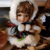Little girl doll wearing a red and green plaid, white fur trimmed outfit