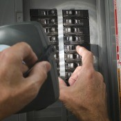 A person looking at a circuit breaker with a flashlight.