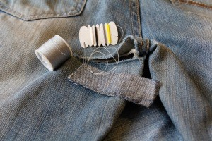 A pair of jeans being mended with needle and thread.