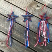4th of July Craft Stick Star with Streamers - three of the star decorations lying on a deck